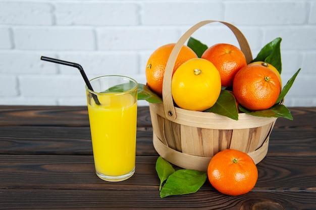 Cesta de frutas cítricas e um copo de suco