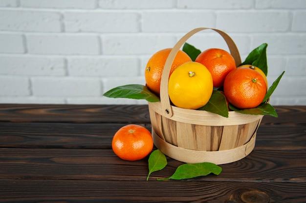 Cesta de frutas cítricas em superfície de madeira
