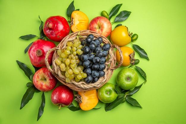 Cesta de frutas coloridas com uvas, romã, maçãs, caquis e folhas