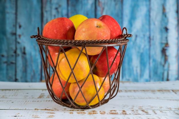 Cesta de frutas de aço com maçãs vermelhas, laranja.