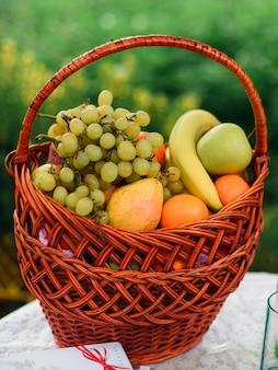 Cesta de frutas de vime com maçãs, uvas, bananas e peras