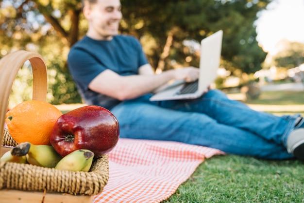 Cesta de frutas perto de homem com laptop
