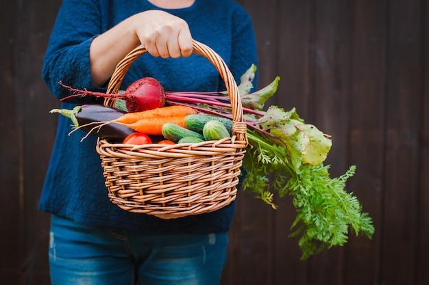 Cesta de legumes nas mãos de um fazendeiro em um de madeira.