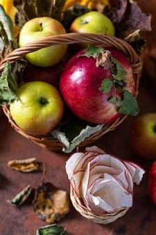 Cesta de maçãs, maçã seca, abobrinha e folhas de outono em uma mesa marrom enferrujada