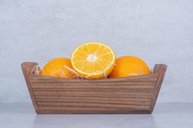 Cesta de madeira cheia de laranjas doces fatiadas
