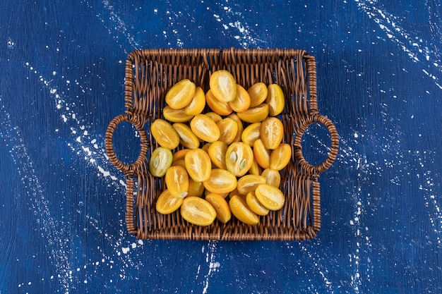 Cesta de madeira com frutas fatiadas de kumquat na mesa de mármore.