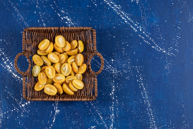 Cesta de madeira com frutas fatiadas de kumquat na superfície de mármore.