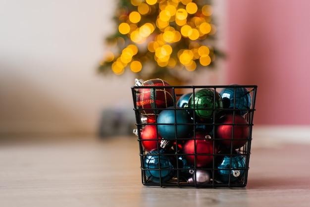 Cesta de metal com brinquedos de bolas de natal nas luzes de natal na árvore