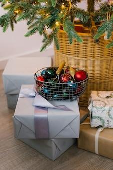 Cesta de metal com brinquedos de natal, caixas de presente e presentes debaixo da árvore de natal