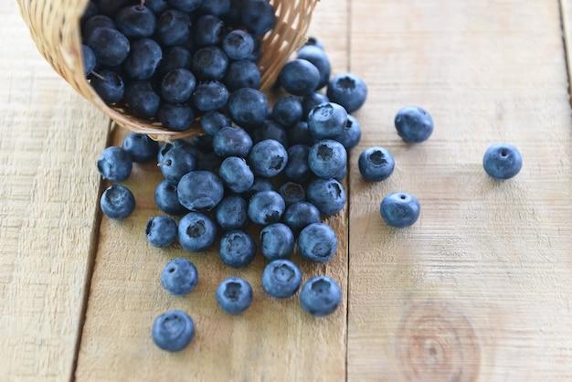 Cesta de mirtilos em uma mesa de madeira - fruta saborosa blueberry fresco