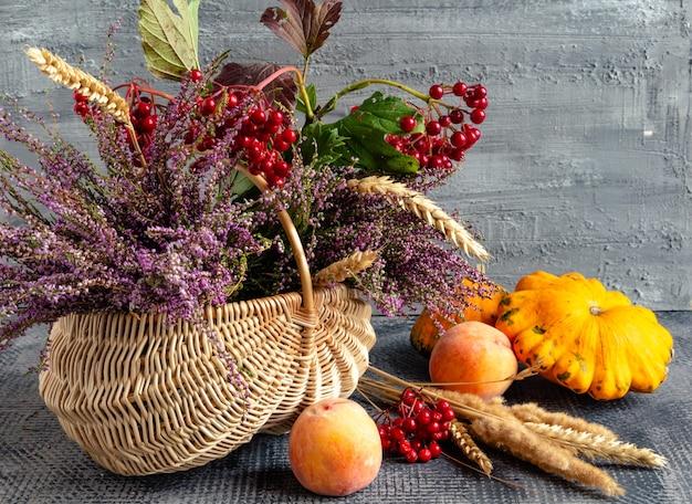 Cesta de outono natureza morta com urze viburnum abóbora pêssego dia de ação de graças