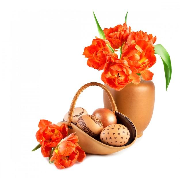 Cesta de ovos de páscoa e buquê de tulipas laranja em vaso de porcelana a condizer