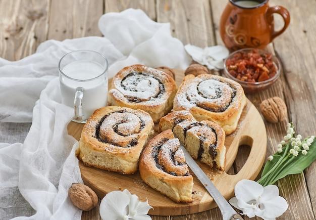 Cesta de pães caseiros com geléia, servida na mesa de madeira velha com nozes e copo de leite