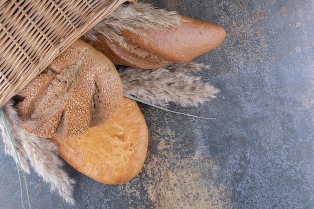Cesta de pães e talos de grama em superfície de mármore