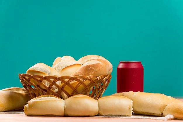 Cesta de pães franceses em uma mesa e uma lata de cola