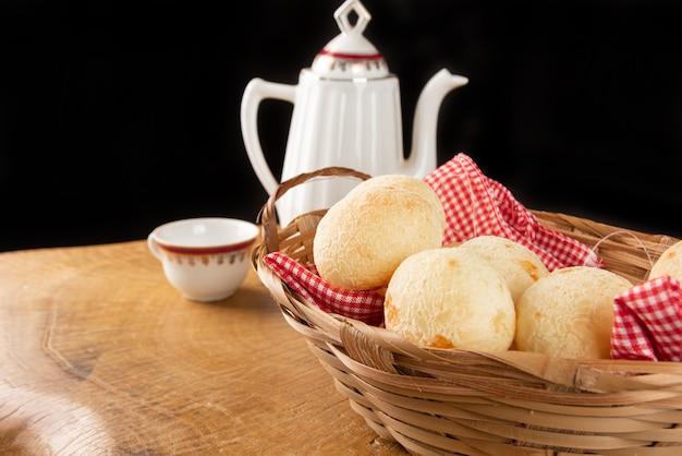Cesta de pano xadrez com pães de queijo em superfície de madeira rústica com bule e xícara de café