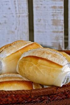 Cesta de pão francês em fundo de madeira rústico