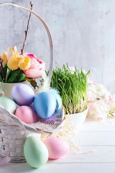 Cesta de páscoa cheia de mão colorido pintado ovos de páscoa, sobre um fundo claro