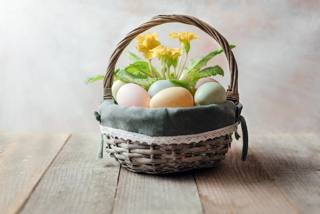 Cesta de páscoa com ovos de páscoa coloridos e galhos de salgueiro na mesa de madeira