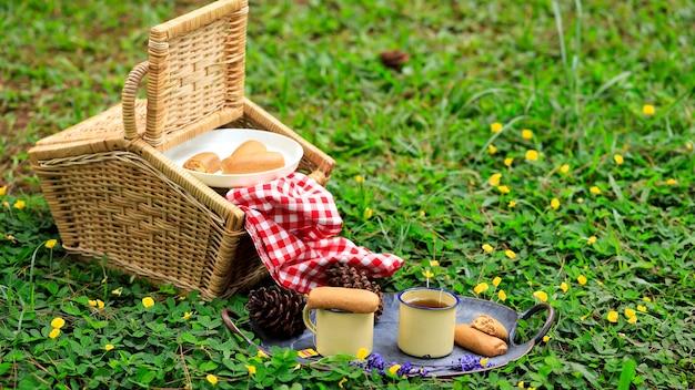 Cesta de piquenique com frutas e padaria na velha mesa de madeira rústica com paisagem verde