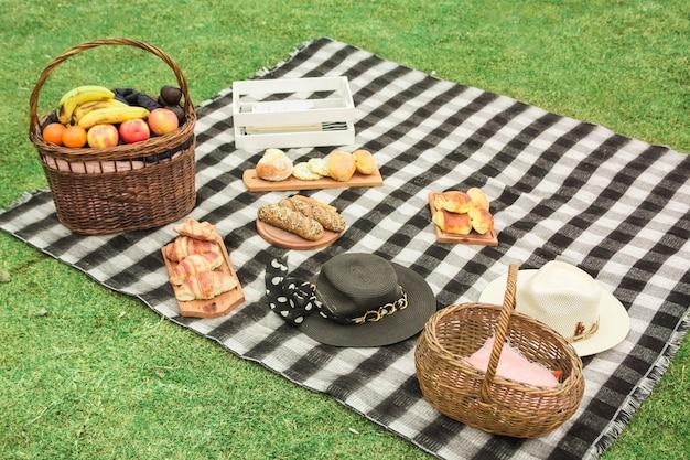 Cesta de piquenique com frutas frescas; pães assados e chapéu no cobertor sobre a grama verde