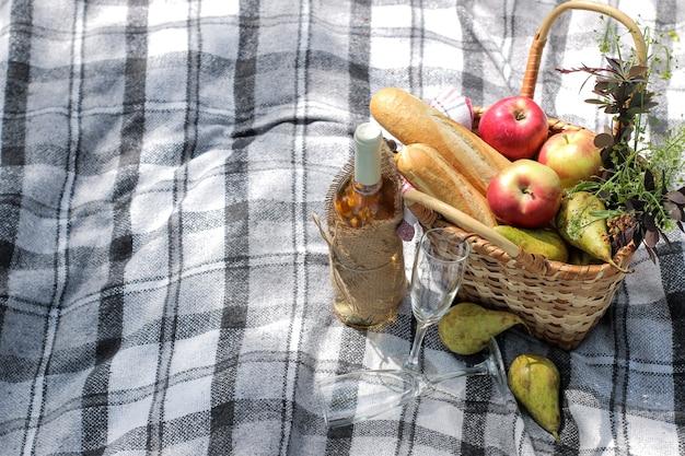 Cesta de piquenique com vinho, frutas e outros produtos em uma manta estampada na grama.