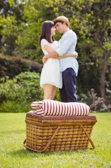 Cesta de piquenique no jardim e casal abraçando uns aos outros