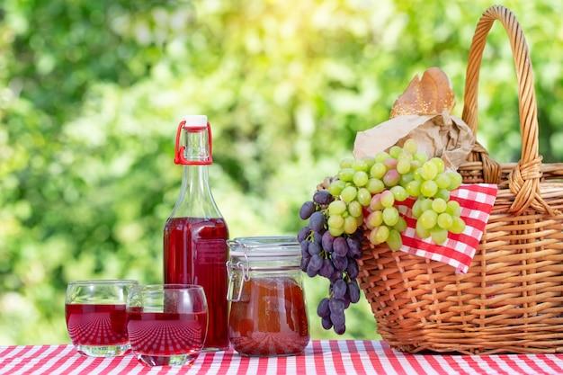 Cesta de piquenique, uvas, suco e geléia numa toalha de mesa vermelha sobre um fundo verde natural
