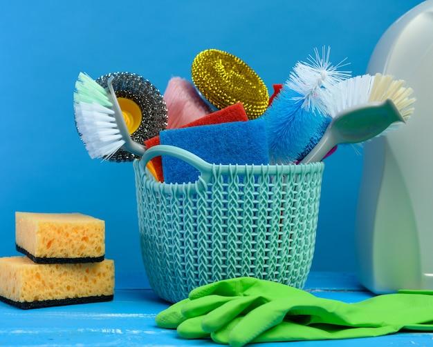 Cesta de plástico azul com escovas, esponjas e luvas de borracha para limpeza, fundo azul