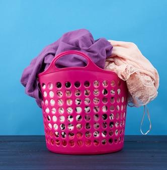 Cesta de plástico rosa cheia de roupas e linho em um espaço azul