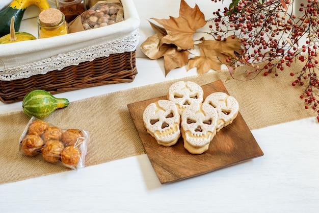 Cesta de presente artesanal com algumas especiarias, abóboras e nozes panelles de piones e biscoitos scull na mesa preparada para embalagem