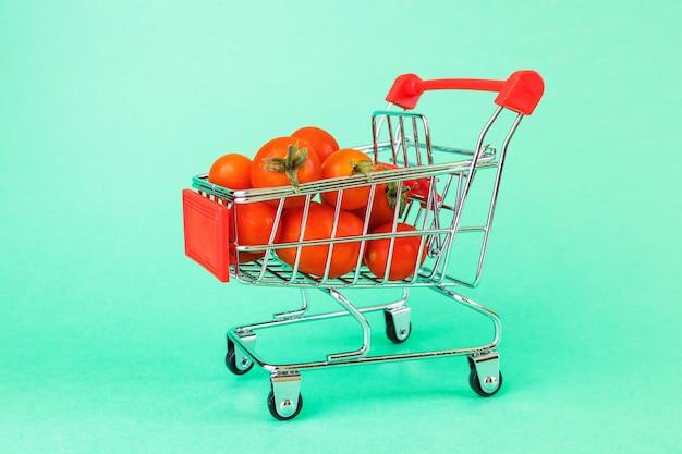 Cesta de supermercado, no interior são tomates cereja maduros.
