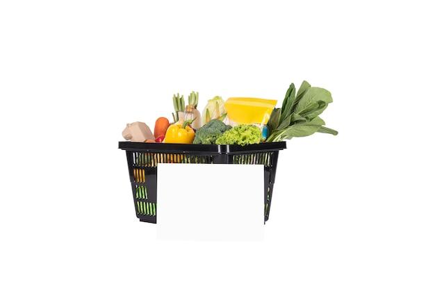 Cesta de supermercado plástica cheia de frutas e vegetais saudáveis, ingredientes com papel vazio de maquete isolado no fundo branco.