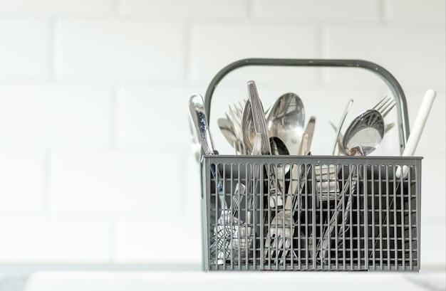Cesta de talheres de plástico cinza para lava-louças com garfo, colher e facas em fundo branco