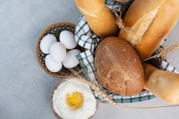 Cesta de vários pães junto com farinha e ovos. foto de alta qualidade