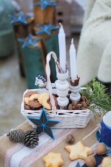 Cesta de vime branco, com biscoitos e nozes e um raminho de abeto