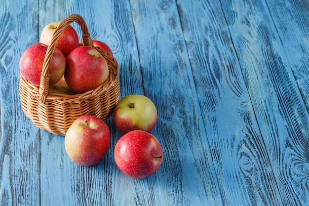 Cesta de vime cheia de maçãs de gala vermelha em fundo de madeira rústica