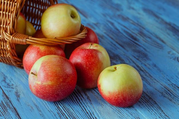 Cesta de vime cheia de maçãs de gala vermelha na superfície de madeira rústica