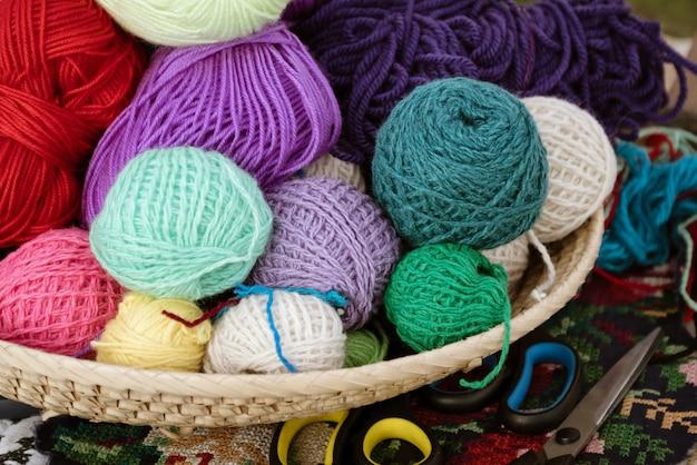 Cesta de vime com bolas multicoloridas de fios de lã para tricô