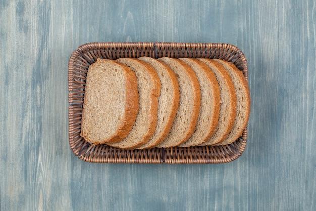 Cesta de vime com fatias de pão de centeio na mesa de pedra.