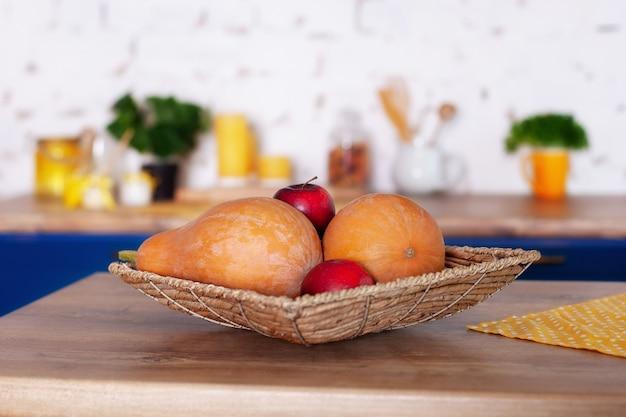Cesta de vime com maçãs e abóboras na cozinha.