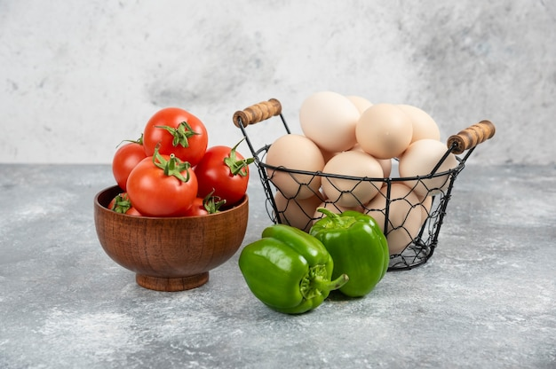Cesta de vime com ovos crus orgânicos, pimentões e tomates vermelhos no mármore.