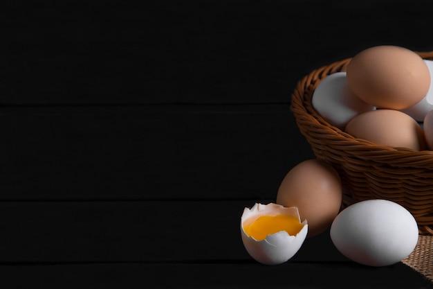 Cesta de vime com ovos de galinha crus na superfície de madeira escura. foto de alta qualidade
