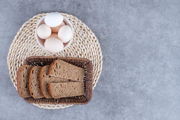 Cesta de vime com pão de centeio e uma tigela de ovos crus na mesa de pedra.