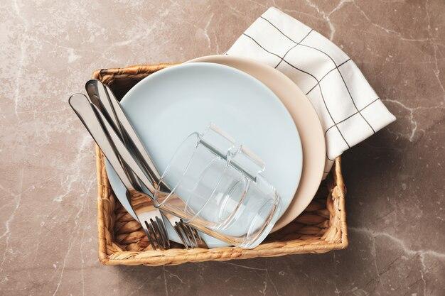 Cesta de vime com pratos, copos e garfos na vista superior cinza
