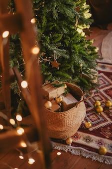 Cesta de vime com presentes e brinquedos para a árvore de natal. decoração de ano novo no interior.