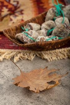 Cesta de vime de caquis doces secos na mesa de pedra.
