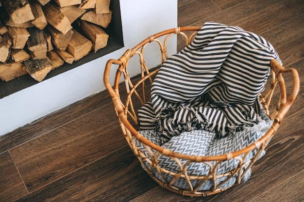 Cesta de vime de madeira com mantas em uma sala, detalhes de interior. conforto do lar.