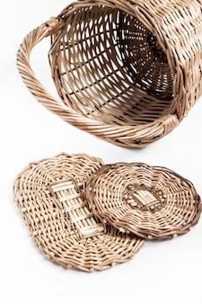 Cesta de vime e fundos para cestas isoladas na superfície branca