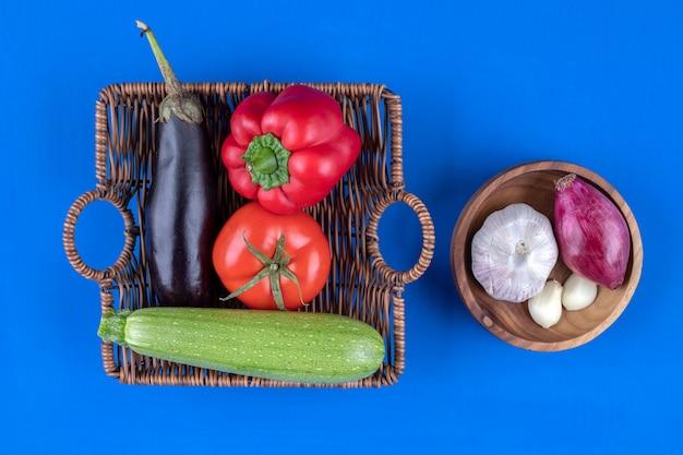Cesta de vime e tigela de legumes frescos colocados sobre uma superfície azul.